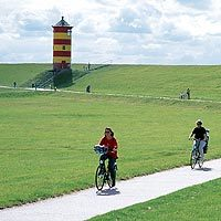 Cyclists in front of Pilsum lighthouse in East Frisia